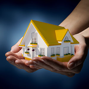 hands holding a small house with a mortgage loan