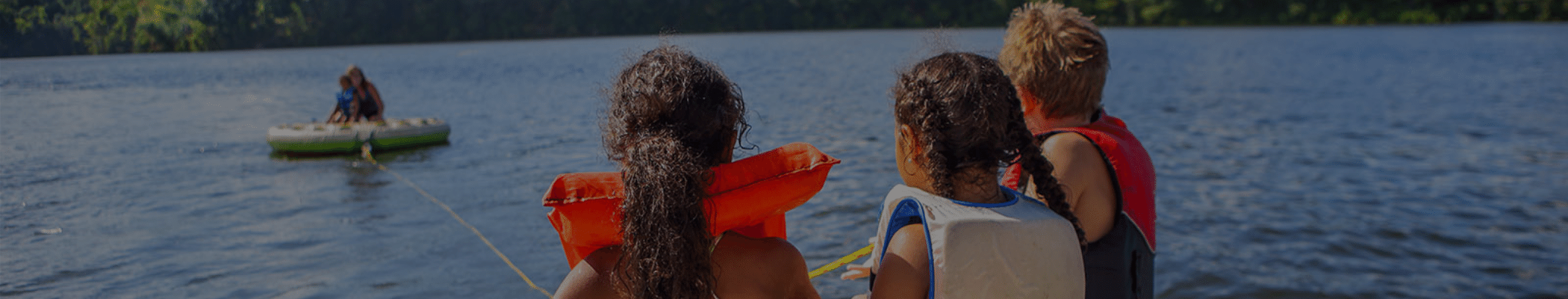 three kids in lifevests looking onto the lake at mom and little brother on a raft